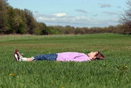 Mergaitė užsimerkusi guli pievoje